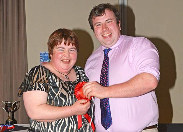 Robert McConnell receiving his prize for holding and restraining a calf section from Wendy Young